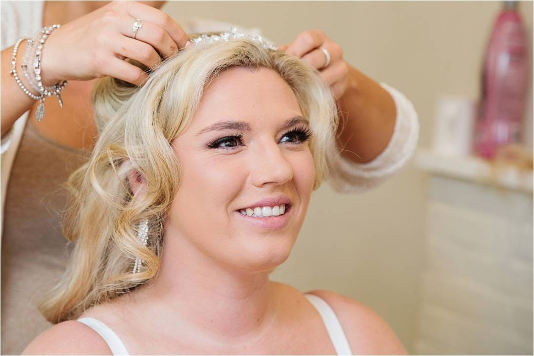 Bride having tiara put on her head by the hairdresser before her wedding ceremony