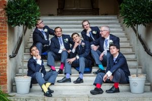 Farnham Castle Wedding photography - Grooms casually sat on stairs showing off their socks